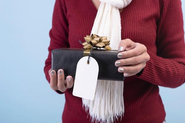 Frauen übergeben das halten des schwarzen geschenkbox- und papiertags lokalisiert auf weißem hintergrund für weihnachts- und des neuen jahreskonzept. Premium Fotos