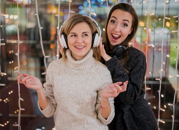 Frauen, welche die kopfhörer haben spaß um weihnachtslichter tragen Kostenlose Fotos