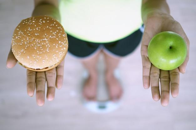 Frauen wiegen mit waage, halten äpfel und hamburger. die entscheidung, junk food zu wählen, das nicht gut für die gesundheit ist, und früchte, die reich an vitamin c sind, sind gut für den körper. diät-konzept Premium Fotos