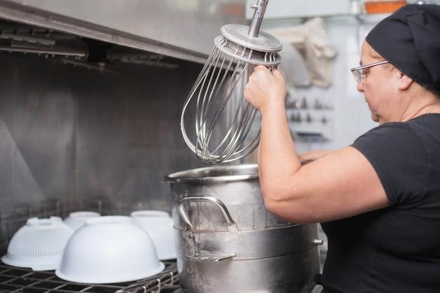 Frauenangestellterladenaufläufe in eine industrielle spülmaschine im restaurant. Premium Fotos
