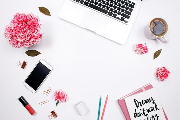 Frauenarbeitsplatz mit notizbuch, rosa gartennelkenblume, auf weißem hintergrund. Premium Fotos