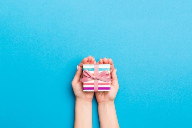 Frauenarme, die geschenkbox mit farbigem band halten Premium Fotos