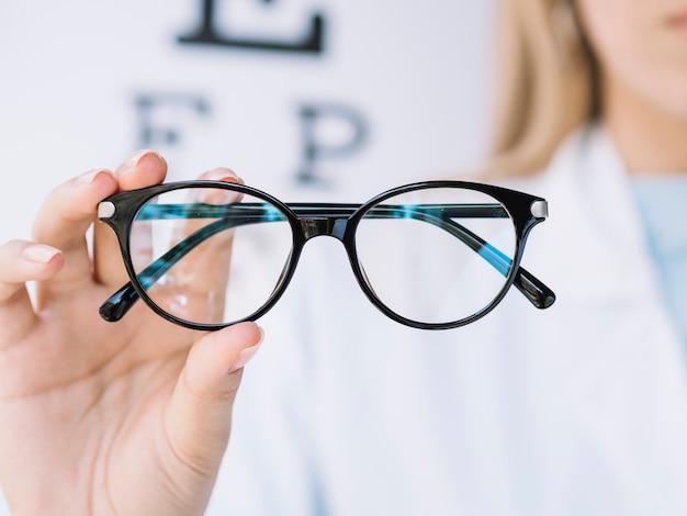 Frauenaugenarzt, der der kamera ein paar brillen zeigt Kostenlose Fotos