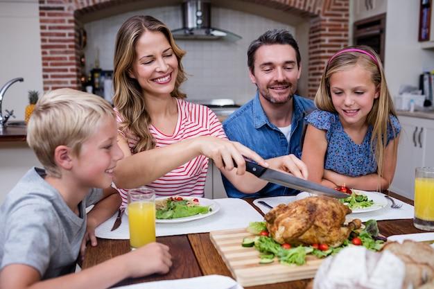 Frauenausschnitt briet truthahn beim essen mit seiner familie Premium Fotos