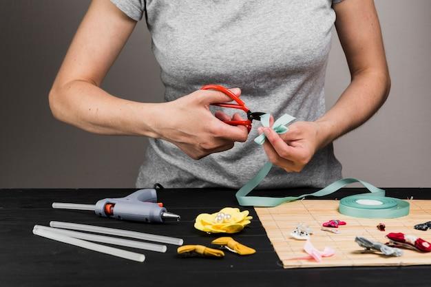 Frauenausschnittband mit schere während der herstellung der verschiedenen haarspange Kostenlose Fotos