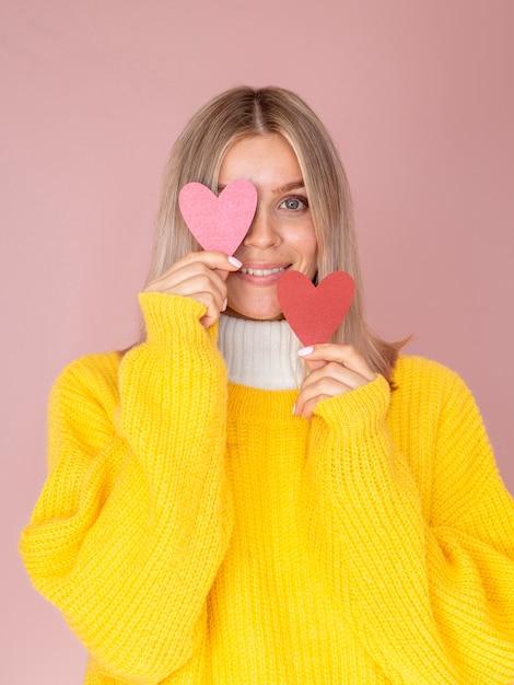 Frauenbedeckungsauge mit papierherzen Kostenlose Fotos