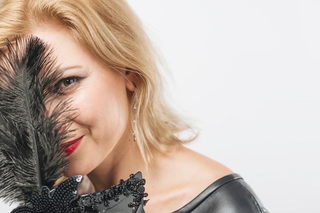 Frauenbedeckungsgesicht mit federn der schwarzen maske Kostenlose Fotos