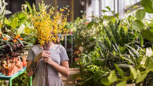 Frauenbedeckungsgesicht mit gelbem blumenblumenstrauß Kostenlose Fotos