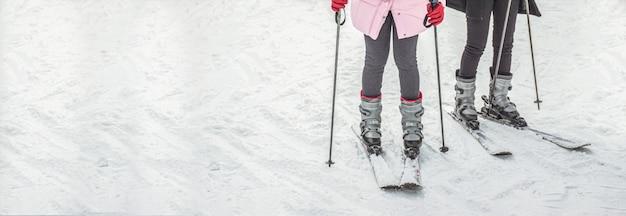 Frauenbeine in den skischuhen auf schnee gestalten mit copyspace, reisende ferien des skibrettes für fahne landschaftlich. Premium Fotos