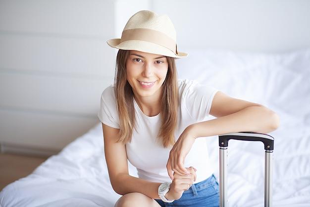 Frauenbeine oben angehoben auf das gepäck, junge frau zu hause, die in bett legt. das weiße schlafzimmer. Premium Fotos