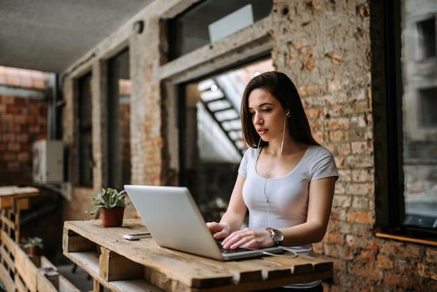 Frauenblogger, der laptop verwendet und kopfhörer trägt. Premium Fotos