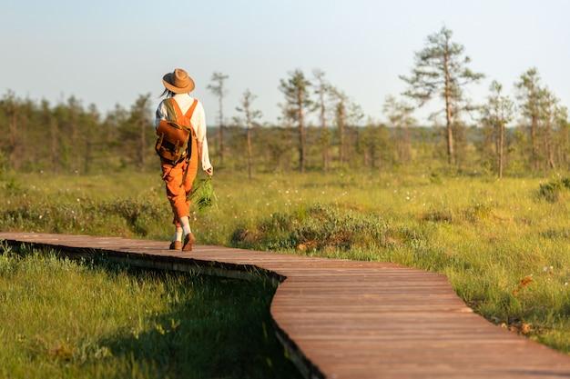 Frauenbotanikerin mit rucksack auf ökologischem wanderweg im sommer im freien. naturforscher, der wildtier- und ökotourismus-abenteuer auf dem weg erkundet Premium Fotos