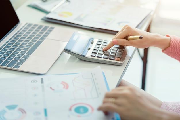 Frauenbuchhalter, der an konten in der geschäftsanalyse mit diagrammen arbeitet und finanzdatenbericht dokumentiert Premium Fotos