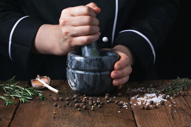 Frauenchef, der gewürze und kräuter zerstößt. Premium Fotos