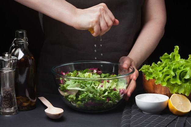 Frauenchef in der küche, die salat zubereitet. Premium Fotos