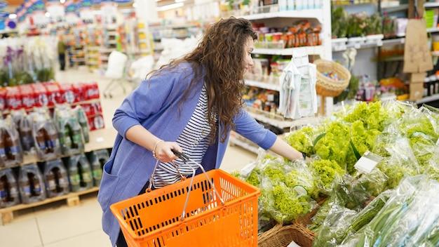 Fraueneinkaufen im supermarkt. junge frau, die aufhebt und grünen blattsalat im gemischtwarenladen wählt. Premium Fotos