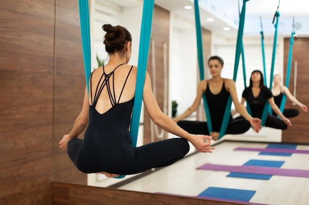 Frauenfall in der hängematte im lotussitz-fliegenyoga, das übungen in der turnhalle ausdehnt Premium Fotos