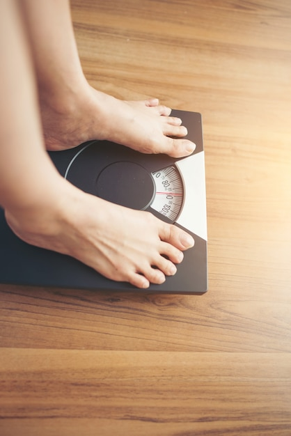 Frauenfüße, die auf gewichtsskala auf hölzernem hintergrund stehen Kostenlose Fotos