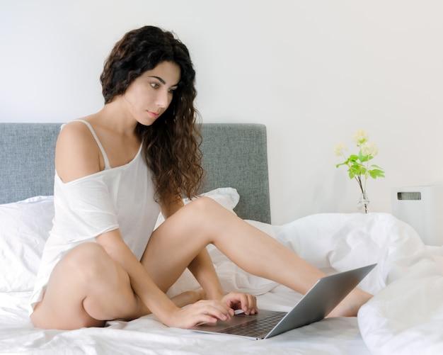 Frauengebrauchslaptop im bett. Premium Fotos