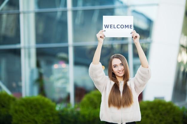 Frauengeschäft mit dem plakat mit willkommensmitteilung Premium Fotos