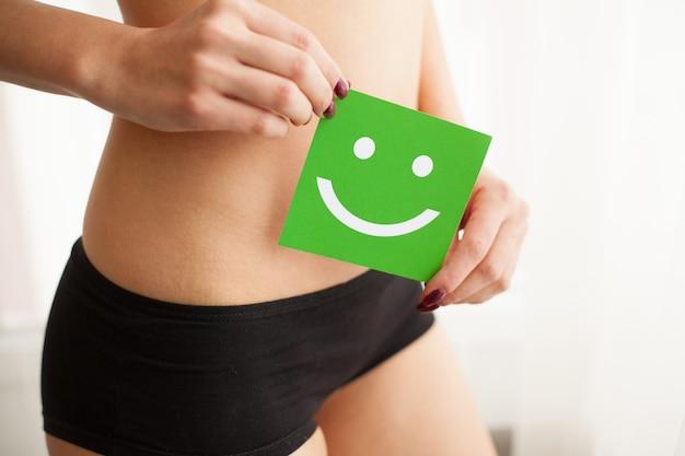 Frauengesundheit. schöner weiblicher körper im schlüpfer mit lächelnkarte Premium Fotos