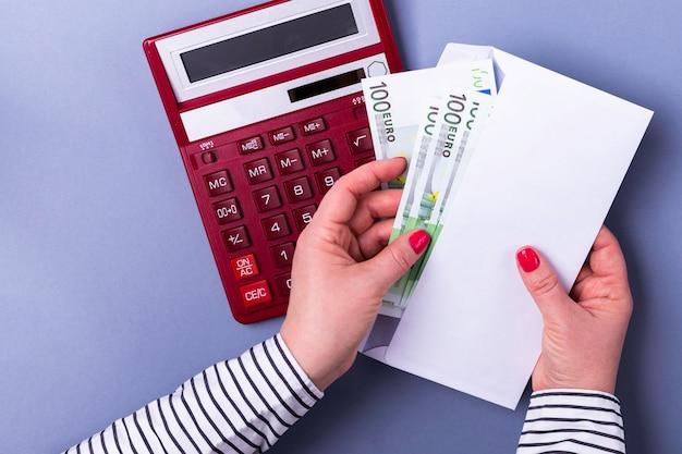 Frauenhändchenhalten, das einen umschlag mit bargeld, taschenrechner, eurobanknoten hält. Premium Fotos