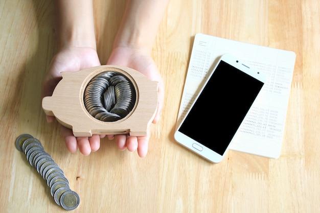 Frauenhände, die auf dem tisch sparschweinholz und einen hintergrund des smartphone halten Premium Fotos