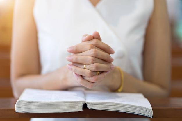 Frauenhände, die auf einer bibel in der kirche für glaubenskonzept, spiritualität und christliche religion beten. Premium Fotos