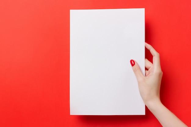 Frauenhände, die ein weiß ein leeres papier a4 auf einem roten hintergrund halten Premium Fotos