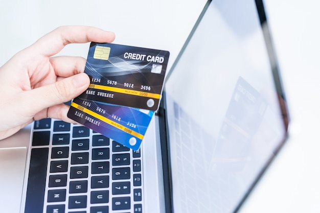 Frauenhände, die eine kreditkarte für online-einkauf halten Premium Fotos