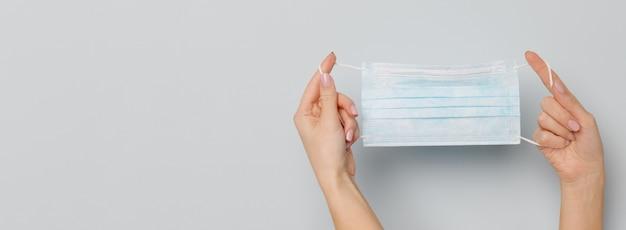 Frauenhände, die eine medizinische gesichtsmaske halten, schutz gegen allergie, virus, covid-19 und coronavirus. Premium Fotos
