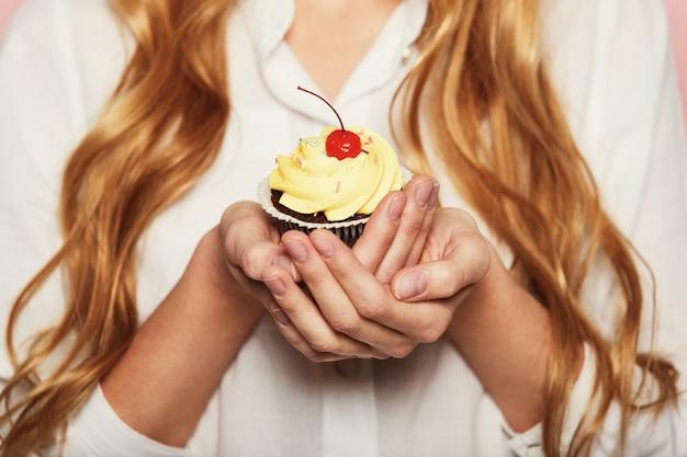 Frauenhände, die einen köstlichen leckeren kleinen kuchen halten Kostenlose Fotos