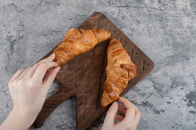 Frauenhände, die frische croissants auf einem hölzernen schneidebrett halten. Kostenlose Fotos