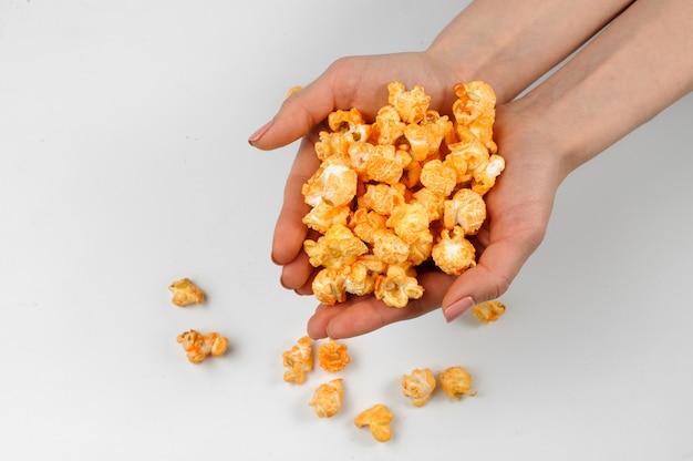 Frauenhände, die frisches und salziges popcorn halten Premium Fotos
