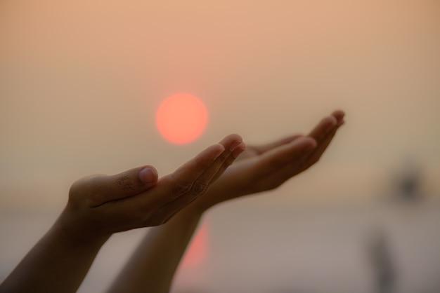 Frauenhände, die für das segnen vom gott während des sonnenunterganghintergrundes beten. hoffnungs-konzept. Premium Fotos
