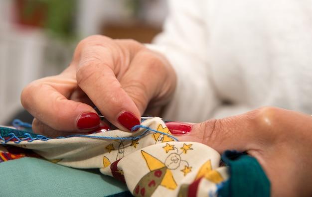 Frauenhände, die für ende eine steppdecke nähen. Premium Fotos