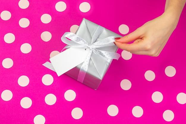 Frauenhände, die geschenkbox auf rosa hintergrund halten Premium Fotos