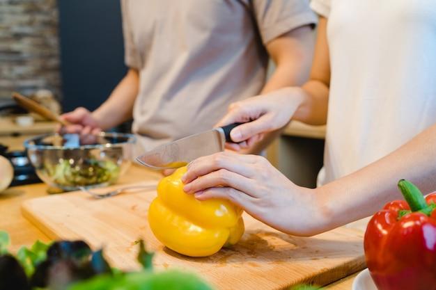 Frauenhände, die grünen pfeffer in der küche schneiden Kostenlose Fotos