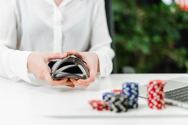 Frauenhände, die karten beim spielen des online-kasinos im büro werfen Premium Fotos