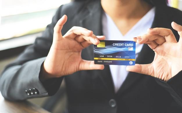 Frauenhände, die kreditkarte für das on-line-einkaufen in einem büro halten Premium Fotos