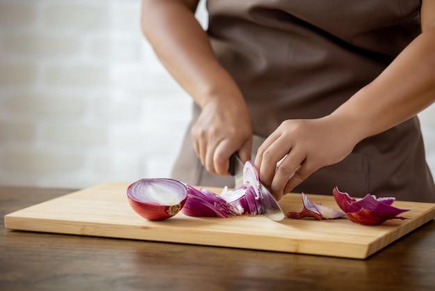 Frauenhände, die rote zwiebel in der küche schneiden Premium Fotos