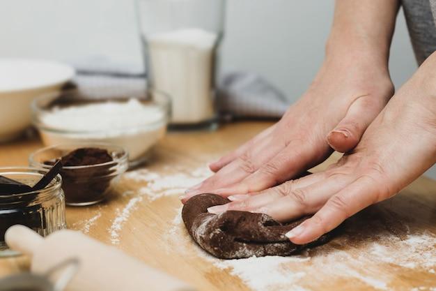 Frauenhände, die schokoladenteig kneten, plätzchen oder nachtisch kochen. zu hause kochen. Premium Fotos