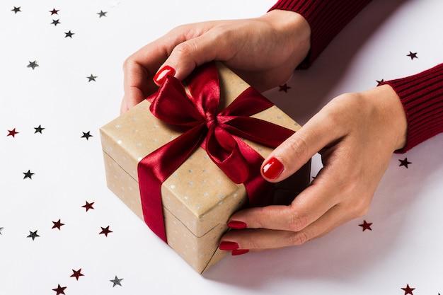 Frauenhände, die weihnachtsferiengeschenkbox auf verzierter festlicher tabelle halten Kostenlose Fotos