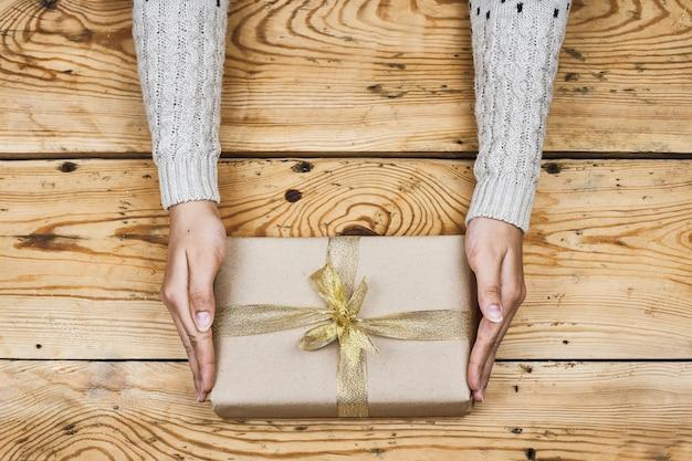 Frauenhände, die weihnachtsgeschenk halten, verbeugten sich mit einem goldenen band Premium Fotos