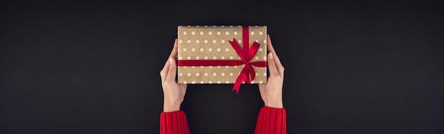Frauenhände, die weihnachtsgeschenkbox auf schwarzem hintergrund geben Premium Fotos