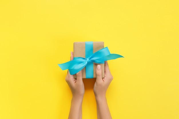 Frauenhände geben eingewickelten valentinsgruß oder anderes handgemachtes geschenk des feiertags im papier mit blauem band. präsentkarton, dekoration des geschenks auf gelber tabelle, draufsicht mit kopienraum Premium Fotos