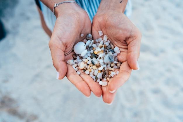 Frauenhände halten viele kleine kieselsteine Kostenlose Fotos