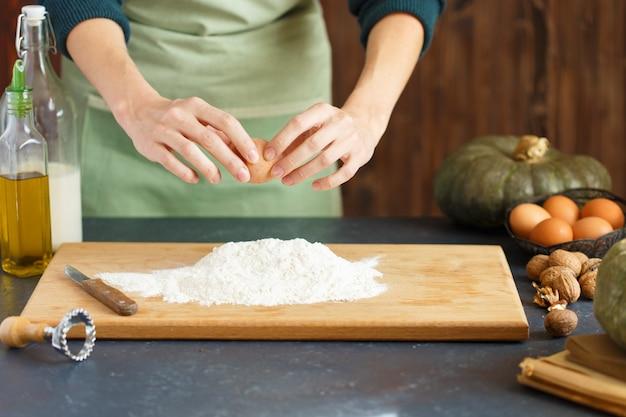 Frauenhände kneten den teig. der konditor treibt ein ei in das mehl. auf dem holztisch sind backzutaten. Premium Fotos