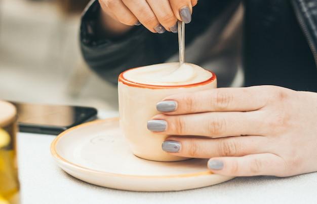Frauenhände mit der maniküre, die draußen eine schale mit capuccino hält Premium Fotos