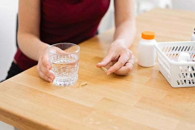 Frauenhände mit ergänzungspillen und glas wasser. Premium Fotos